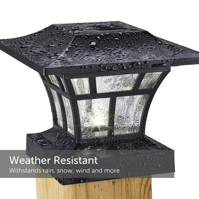 Black ribbed solar post cap light after a rainstorm still illuminated and mounted on a 4X4 post - weather resistant