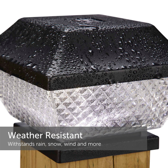Black diamond solar post cap light drenched in rain and mounted on a 4X4 post - weather resistant