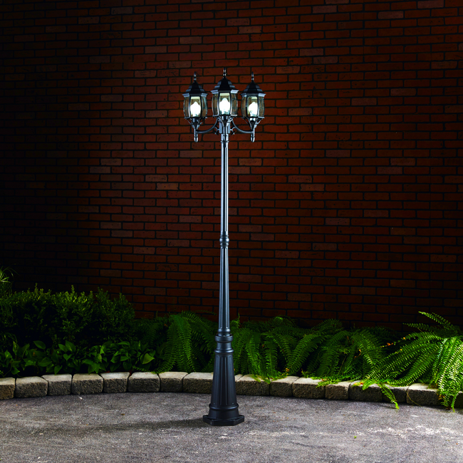 Black lamp post installed in concrete and surrounded by a garden