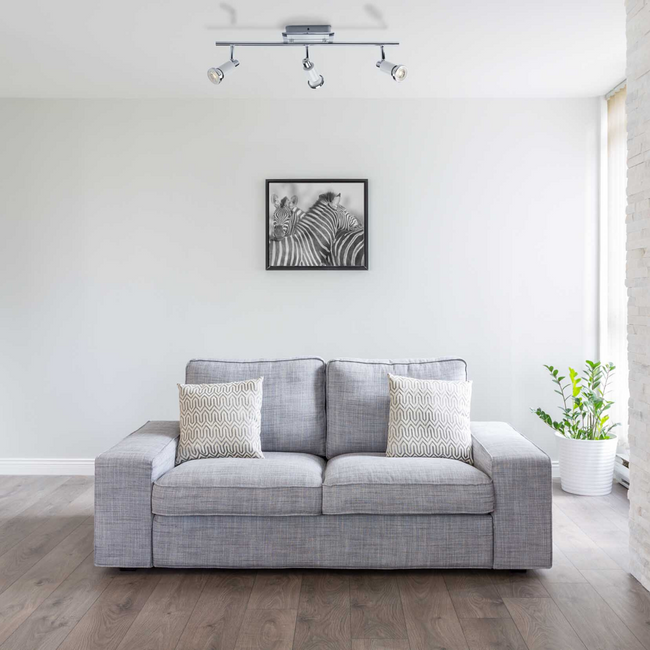 Living room with the Herly Track Lighting Kit hanging over a grey and white couch.