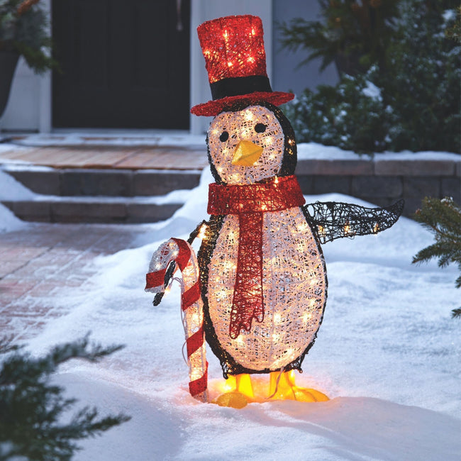 NOMA 2.75 Ft Pre-Lit Incandescent Penguin with Top Hat, Candy Cane and Warm White Bulbs, Outdoors on Snow. Brick Pathway to House Entrance in Background.