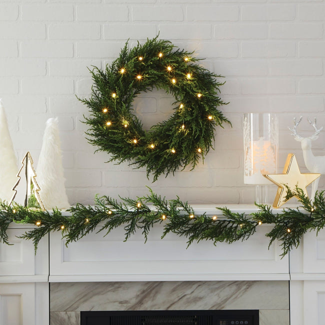 Cedar Wreath Lit Up on White Tiled Wall Background Above Fireplace Mantle. Mantle is Decorated with Cedar Garland and Other Modern Christmas Decor