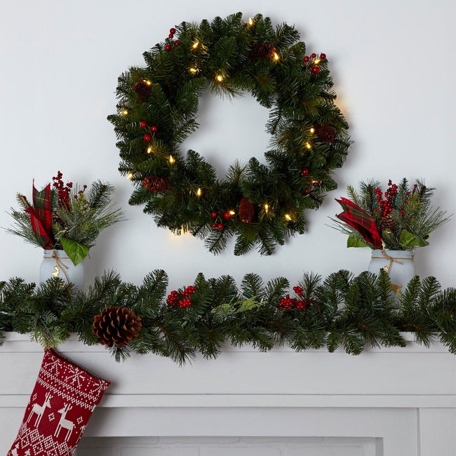NOMA 24-inch Carolina Classic Wreath with Warm White Lights. Wreath on White Wall Above Fireplace Mantel. Mantel Decorated with Carolina Garland.