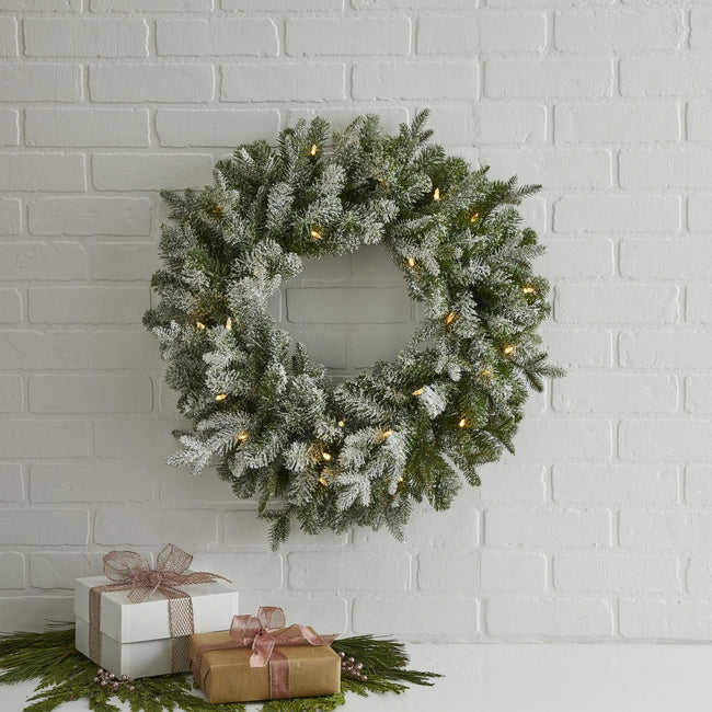 Frosted Fir Wreath on White Tiled Wall. Gift Boxes on White Table Below