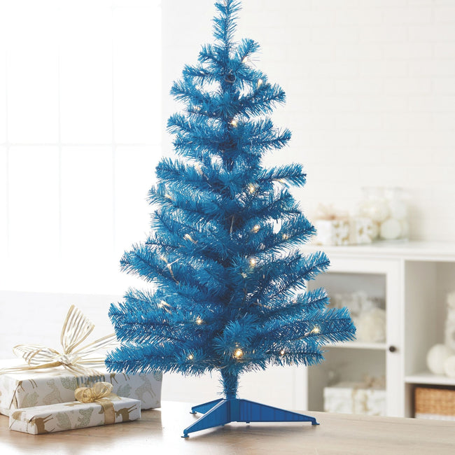 Blue Table Top Tree with Warm White Lights indoors placed on Table with Wrapped Presents