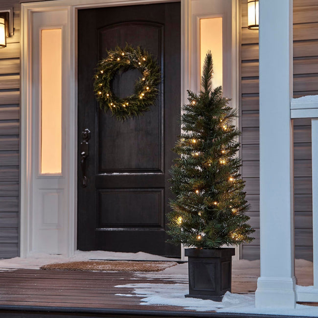 NOMA 4 Ft Farrow Potted Christmas Tree on Porch Entrance infront of Door. Wreath on Door, Snow on Deck/Floor of Porch