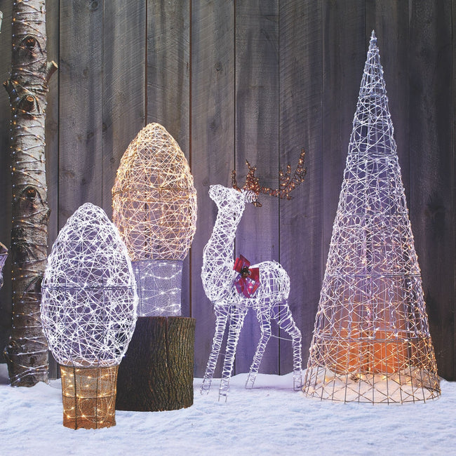 NOMA Micro-Brite Deer Center of Image. On Left 2 Contemporary Large C9 Bulb Wire-forms. On Right Side is Tall Contemporary Cone Tree. Outdoors infront of Wooden Panel Wall. Tree Trunk on Far Left Side, Snow on Ground.