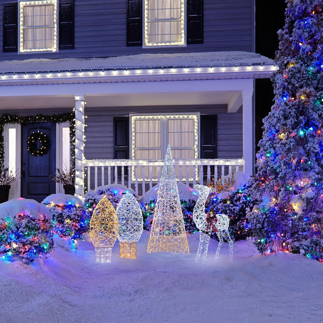 Outdoor Lifestyle Image. Micro-Brite Deer, Cone Tree, C9 Shaped Bulb Wireforms on Snow Covered Lawn. Surrounded by Bushes with Christmas Lights. Christmas Tree on Right Decorated with Multi-Color Christmas Lights. House in Background with Holiday Decorated Porch