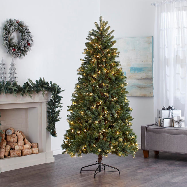 Hudson Spruce Christmas Tree with Warm White Lights,  in Living Room In Front of Fireplace. Fireplace Decorated with Garland and Wreath Above on Wall, Giftboxes to Right of the Tree on Ottoman.