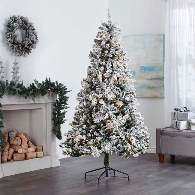 Flocked Cypress Christmas Tree with Warm White Lights, in Living Room In Front of Fireplace. Fireplace Decorated with Garland and Wreath Above on Wall, Giftboxes to Right of the Tree on Ottoman.