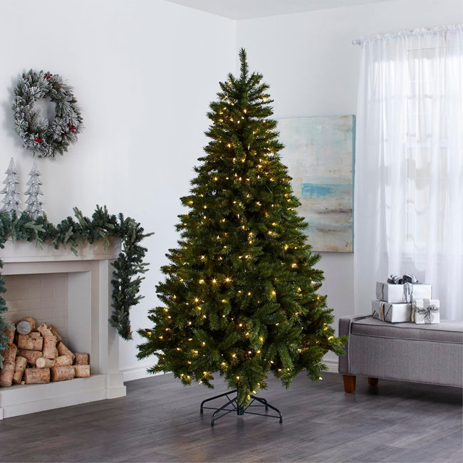 Henry Fir Christmas Tree with Warm White Lights,  in Living Room In Front of Fireplace. Fireplace Decorated with Garland and Wreath Above on Wall, Giftboxes to Right of the Tree on Ottoman.