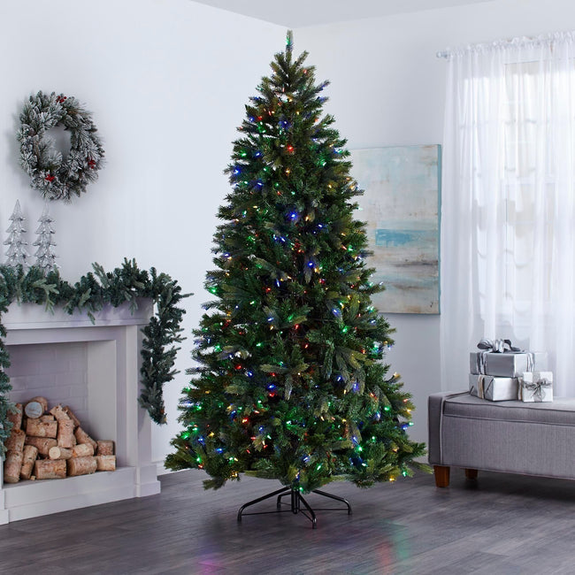 Colorado Christmas Tree with Multi-Color Lights, in Living Room In Front of Fireplace. Fireplace Decorated with Garland and Wreath Above on Wall, Giftboxes to Right of the Tree on Ottoman.