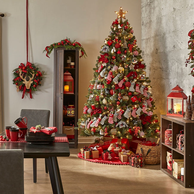 Heavily Decorated Winston Spruce on Right Side Next to Concrete Wall. Room is Decorated with Christmas Decor, Wreaths, Gift boxes and Red Colored Decor. Red Color Scheme.