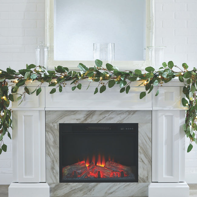 Eucalyptus Garland with Warm White Lights on Fireplace Mantel. White Wall and White Marble Fireplace. Fireplace is Lit