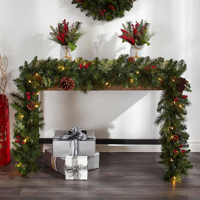 Preston Berry Garland Decorating the Front View of Table. Silver Boxed Presents on Wooden Floor. Two Potted Plant Decorations on Top of Table. Partially Visible Wreath on Wall. White Wall Background.