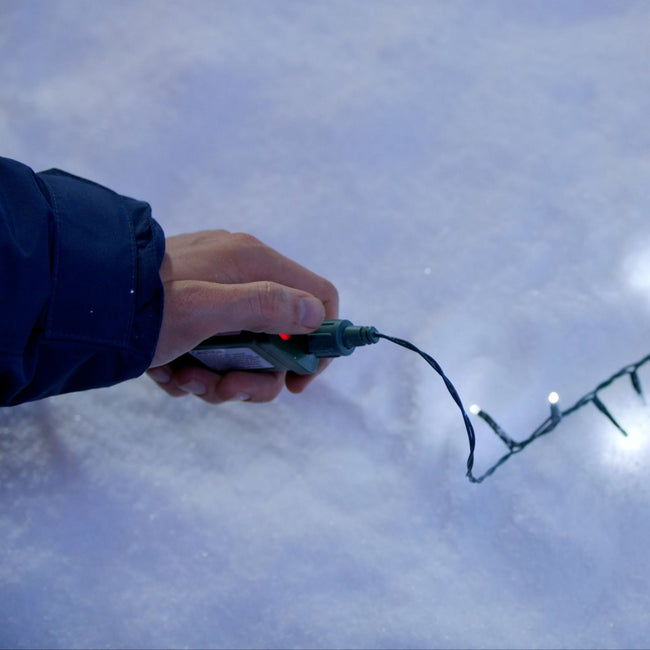 Hand holding control switch for Cluster Lights. Green Wire. Displayed on Snow