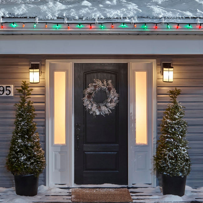 Noma C6 Red & Green String Lights, on a roof edge above home entrance. Wreath on door and two potted trees on porch