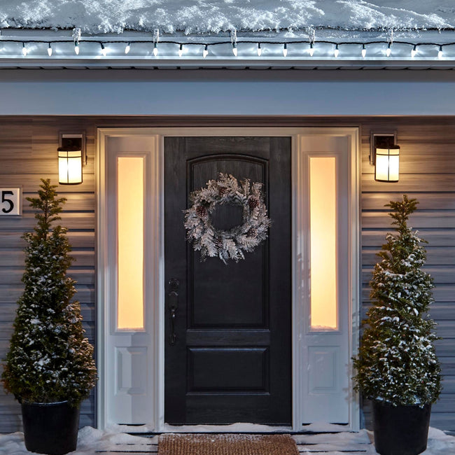 Noma C6 Pure White String Lights on a roof edge above home entrance. Wreath on door and two potted trees on porch
