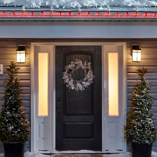 Noma C6 Red String Lights on a roof edge above home entrance. Wreath on door and two potted trees on porch