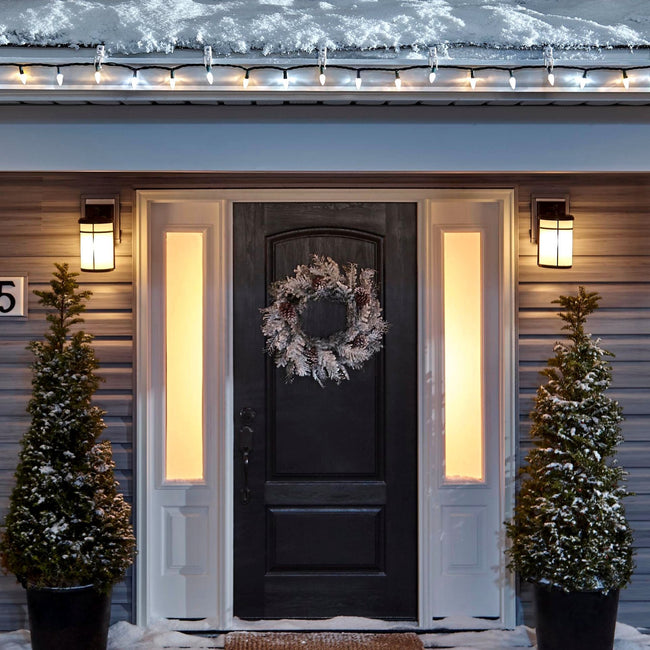 Noma C6 Warm & Pure White String Lights, on a roof edge above home entrance. Wreath on door and two potted trees on porch
