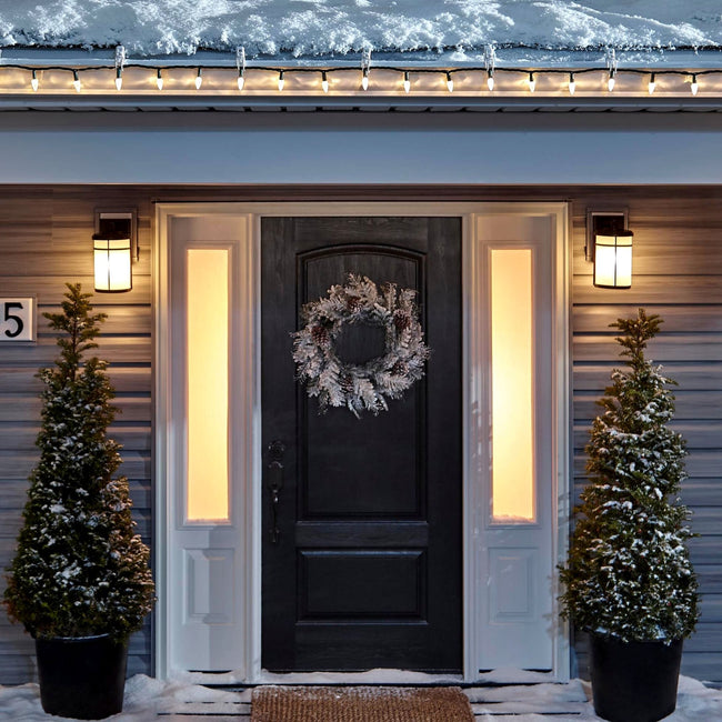 Noma C6 Warm White String Lights, on a roof edge above home entrance. Wreath on door and two potted trees on porch