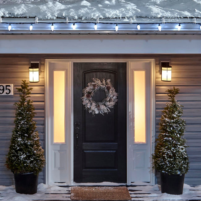 Noma C9 Cool White String Lights, on a roof edge above home entrance. Wreath on door and two potted trees on porch