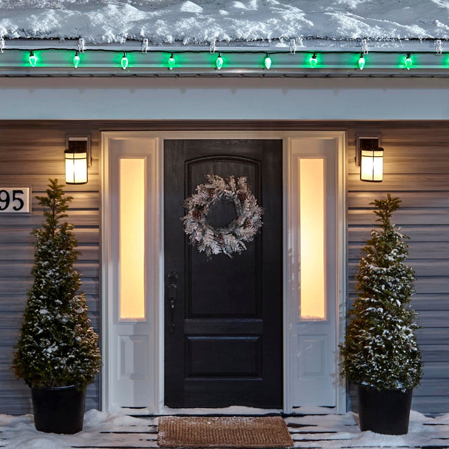Noma C9 Green String Lights, on a roof edge above home entrance. Wreath on door and two potted trees on porch