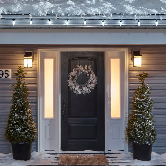 Noma C9 Pure White String Lights, on a roof edge above home entrance. Wreath on door and two potted trees on porch