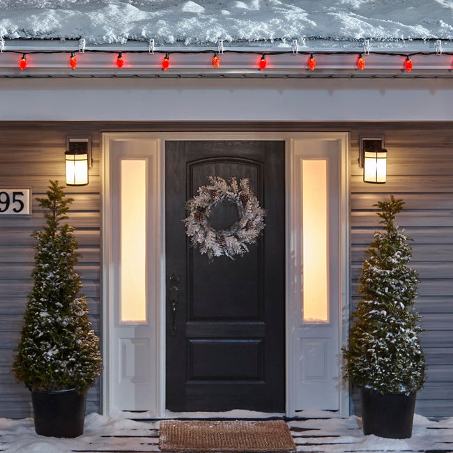 Noma C9 Red String Lights, on a roof edge above home entrance. Wreath on door and two potted trees on porch