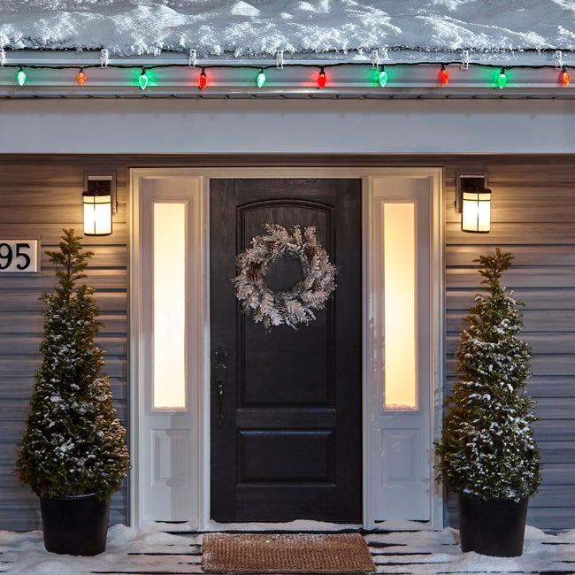 Noma C9 Red & Green String Lights, on a roof edge above home entrance. Wreath on door and two potted trees on porch