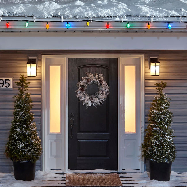Noma C9 Multi-Color String Lights, on a roof edge above home entrance. Wreath on door and two potted trees on porch