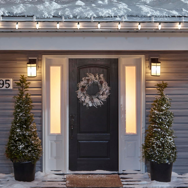 Noma C9 Warm White String Lights, on a roof edge above home entrance. Wreath on door and two potted trees on porch
