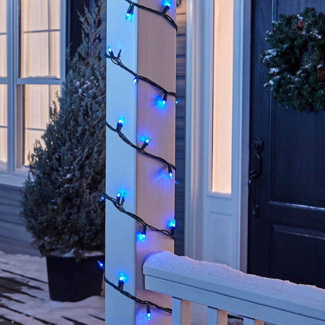 NOMA Blue Mini LED String Lights, Wrapped Around Porch Pillar. In background: Potted Tree, and Wreath on Door