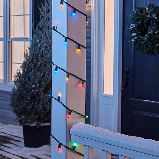 NOMA Multi-Color Mini LED String Lights, Wrapped Around Porch Pillar. In background: Potted Tree, and Wreath on Door