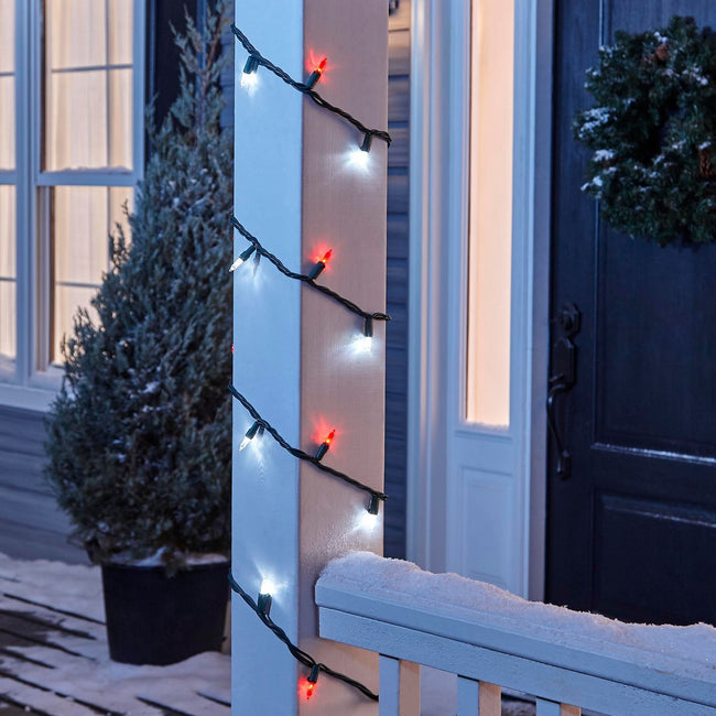 NOMA Red & Pure White Mini LED String Lights, Wrapped Around Porch Pillar. In background: Potted Tree, and Wreath on Door