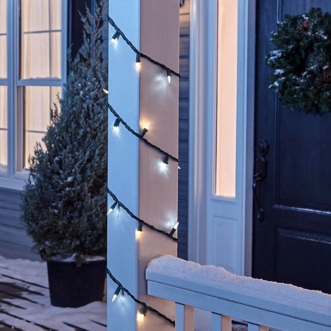 NOMA Warm & Pure White Mini LED String Lights, Wrapped Around Porch Pillar. In background: Potted Tree, and Wreath on Door