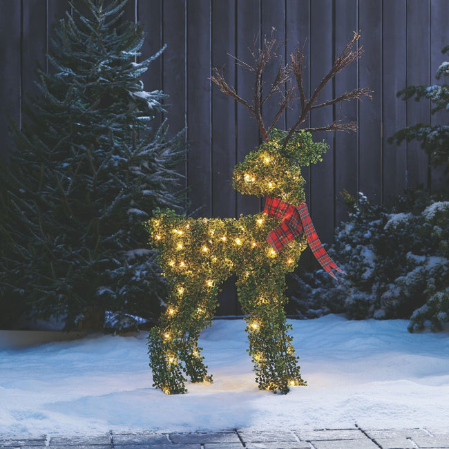NOMA 4.4 Ft Pre-Lit Incandescent Winter Garden Deer, Outdoors on Snow. Pine Trees and Brown Wooden Fence in Background.