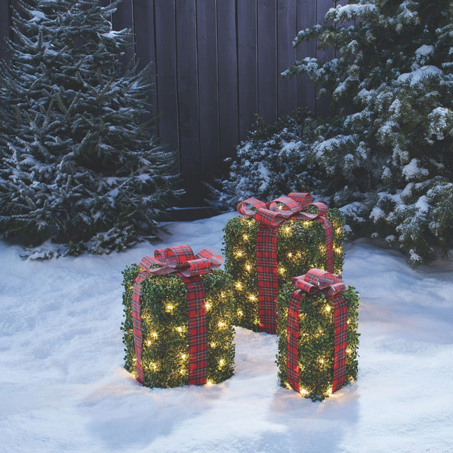 NOMA Incandescent Winter Garden Gift Boxes, 3-Pack - On Snow Covered Lawn. Trees and Wooden Fence in Background.