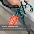 Hand Attaching C9 Quick Clip to Roof Edge or Railing. Text reads: Hang in Half the Time