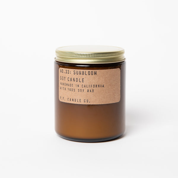 PF Candle Co San Francisco Sunbloom scented soy wax candles are hand-poured into apothecary inspired amber jars with our signature kraft label and a brass lid