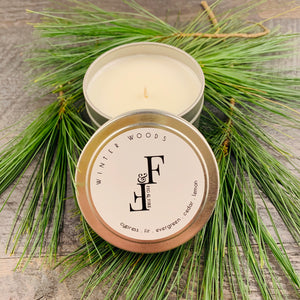 Handcrafted winter candle - scent is winter woods - smells of cypress, fir, evergreen, cedar, and lemon - all natural soy candle - vegan, non-toxic, made with essential oils - container is a silver tin - seasonal collection