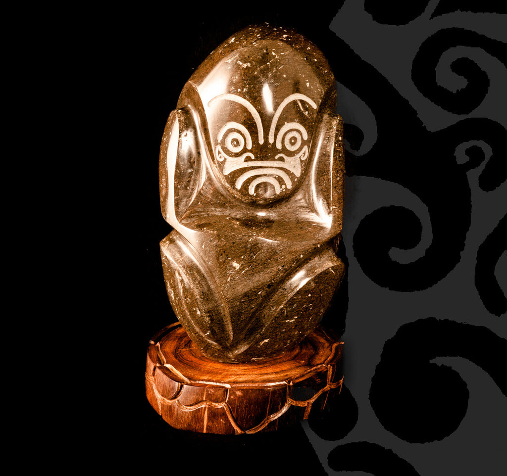 Tiki Sculpted in Dark Stone on a Wooden Pedestal