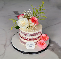 Naked cake layered with frosting, decorated with fresh flowers and roses