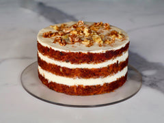 naked carrot cake layered with cream cheese frosting topped with crushed walnuts