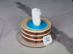 Carrot naked cake layered with cream cheese, topped with a handmade Singapore merlion fondant figure