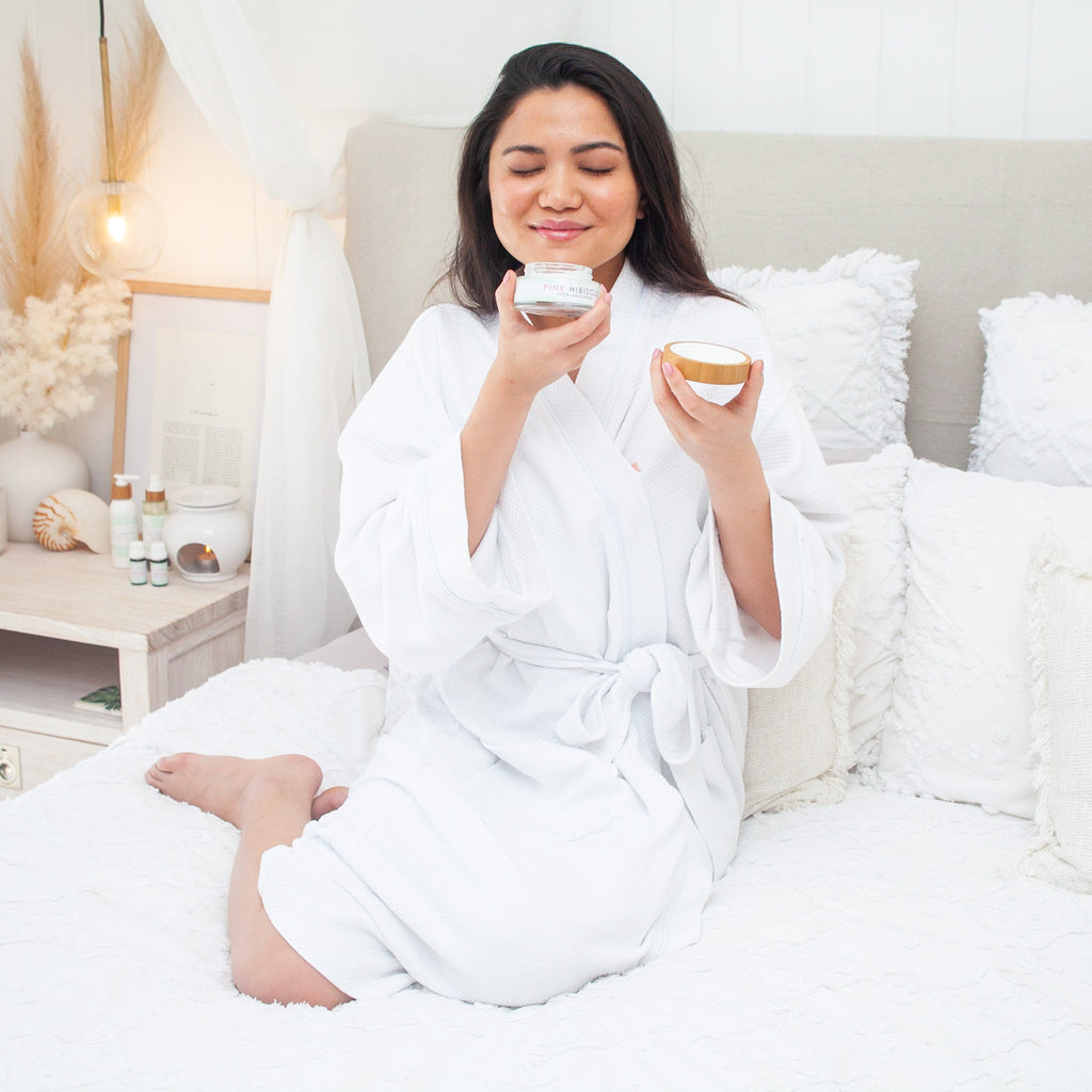Filipino woman smelling Pink Hibiscus Facial Moisturiser in Hamptons-style bed wearing a white robe