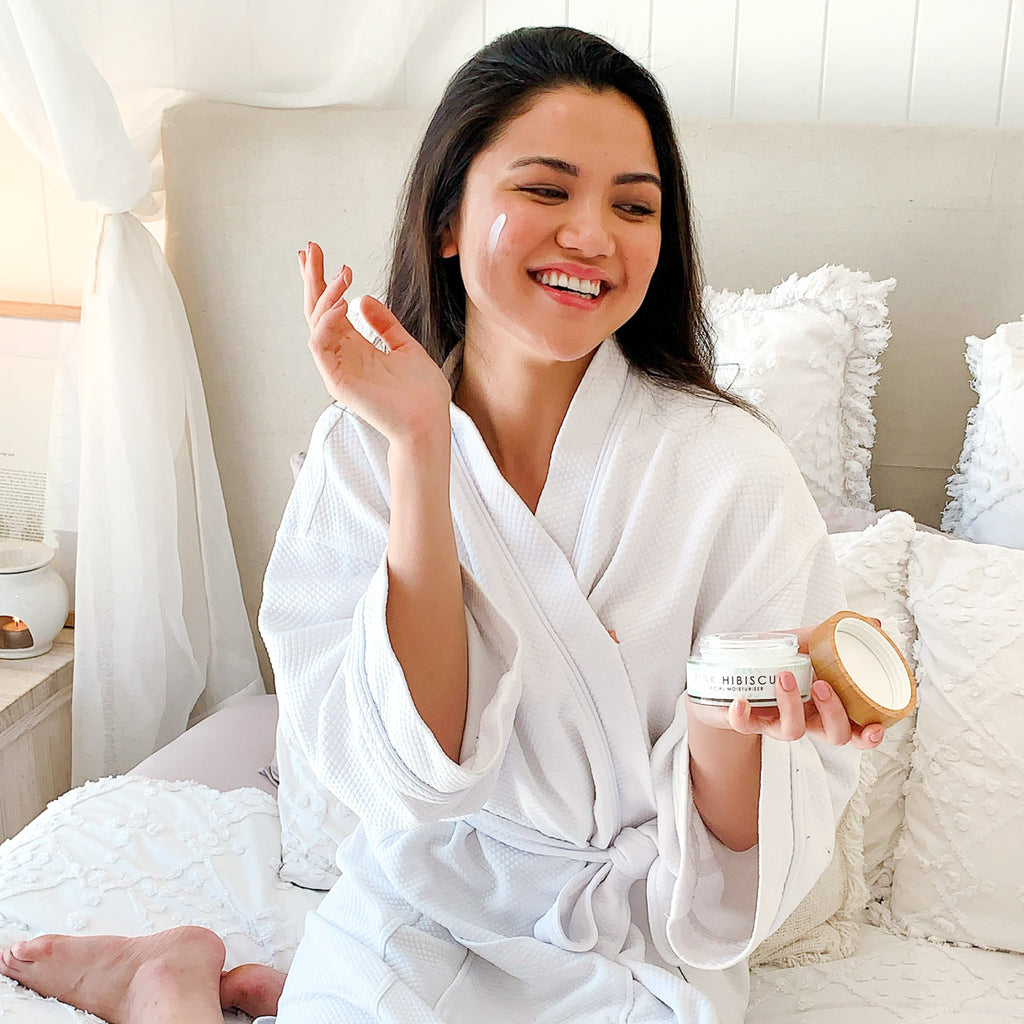 Filipino woman applying Pink Hibiscus Facial Moisturiser to her face in Hamptons-style bed wearing a white robe