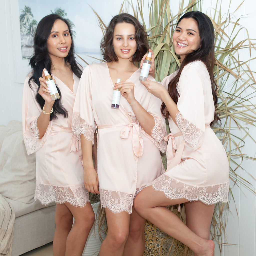 A Thai, Australian and Filipino woman in pink robes posing with Pink Hibiscus Facial Spritzes