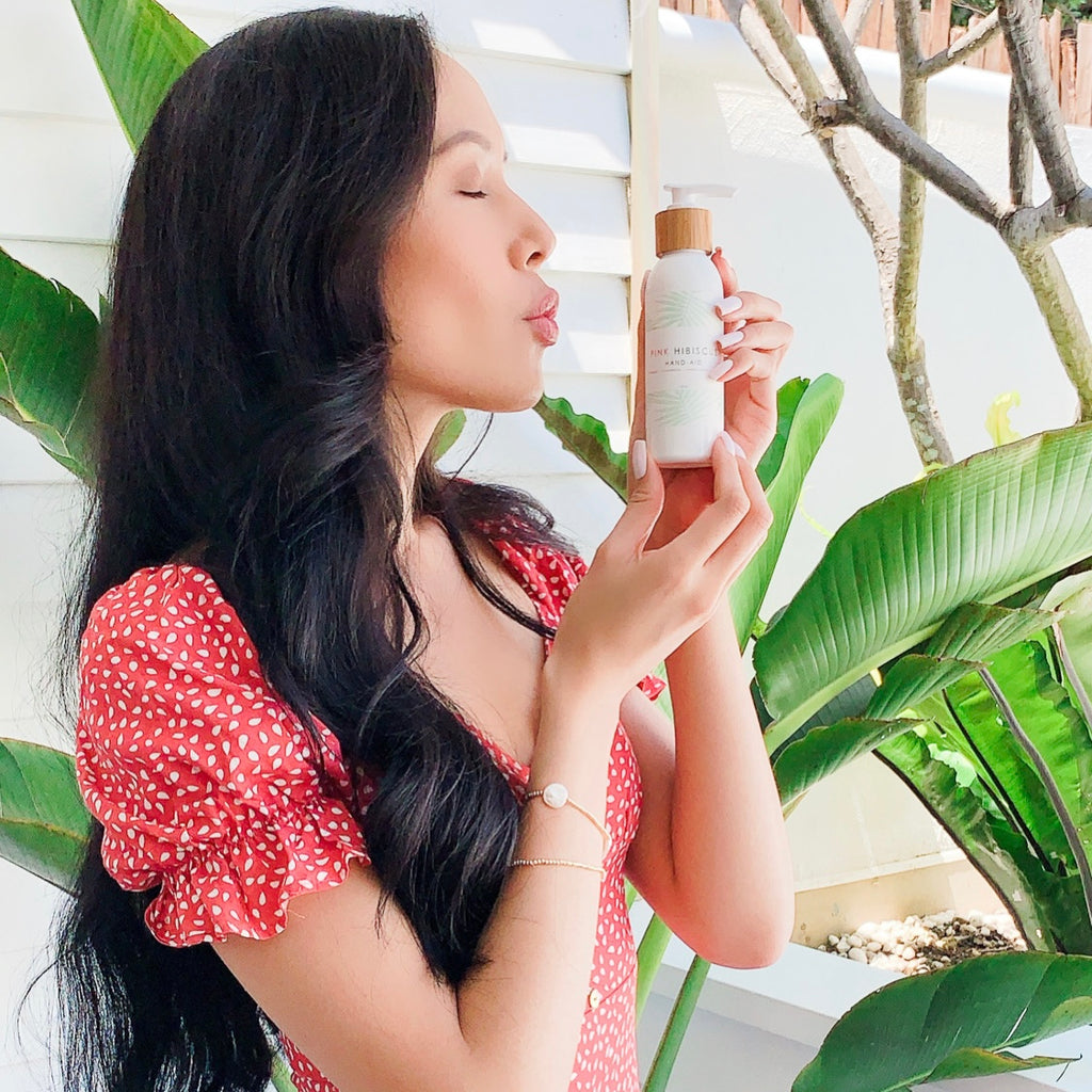 Thai woman kissing Pink Hibiscus Hand-Aid Healing Hand Balm with traveller palm behind h er
