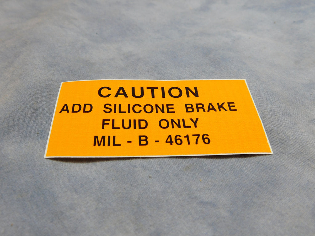 """CAUTION ADD SILICONE BRAKE FLUID ONLY MIL-B-46176""  PART # 12302516 NSN 7690-01-111-2265"